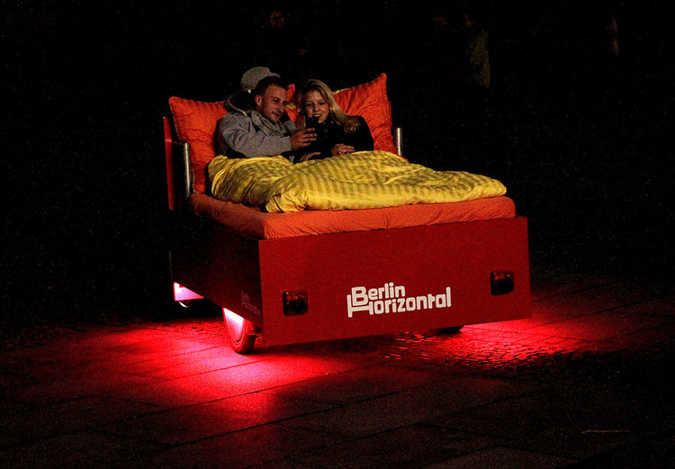 a couple lying on a bed which is driven by a bike throu the night of Berlin Bed Bicycle Bike Bike Taxi Celebrate Your Ride Cool Couple Enjoying Life Festival Of Lights Fun Happiness Lights Love Night Red Relaxation Togetherness Tourists Travel Wheels