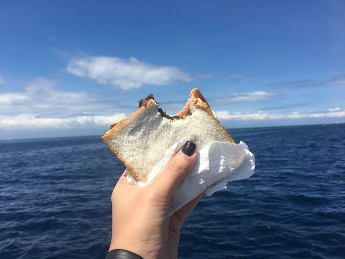 Close-up of hand holding sandwich by sea against blue sky