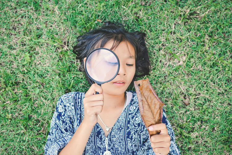 High angle view of girl holding magnifying glass on face while lying on grassy field