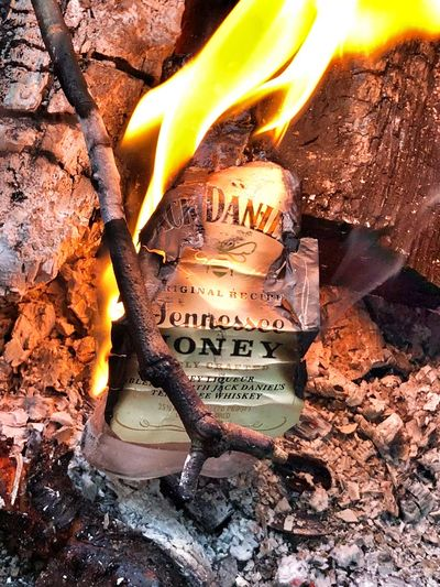 Goes down smooth but watch the after burn VSCO Vscocam Whiskey Jack Daniels Campfire Camping Nature No People High Angle View Text Day Container Fire Burning Outdoors