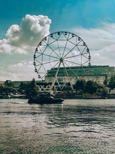 Ferris wheel by river against sky
