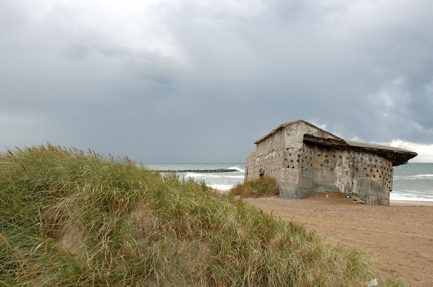 """Remains of the """"Atlantic Wall"""" at the beach in Denmark. These Bunkers remain at the beach after having been abandoned at the end of WW2 Bunker Nature WW2 Leftovers Abandoned Architecture Beach Building Exterior Built Structure Cloud - Sky Day Fortress Grass Horizon Over Water Landscape Nature No People Outdoors Sand Sea Sky Stronghold Water Ww2"""