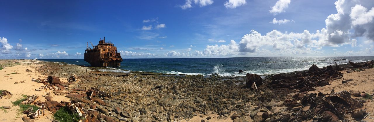 Rusted stranded ship on coast of Klein-Curacao Blue Sky And Clouds Stranded Boat Panoramic Photography Coast Rusty Metal