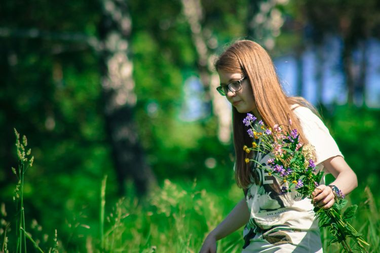 Woman holding flower while walking on field