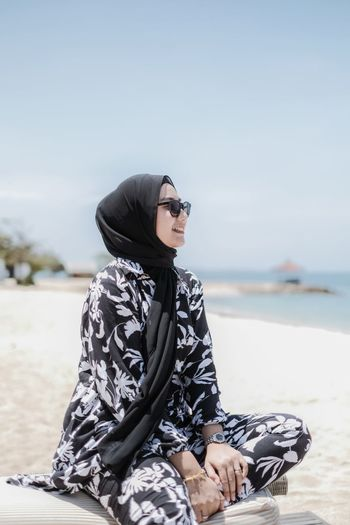 Woman wearing sunglasses sitting at beach