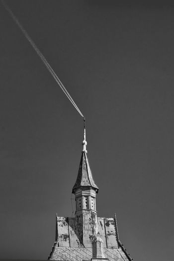 Low angle view of building against clear sky and an airplane's trail