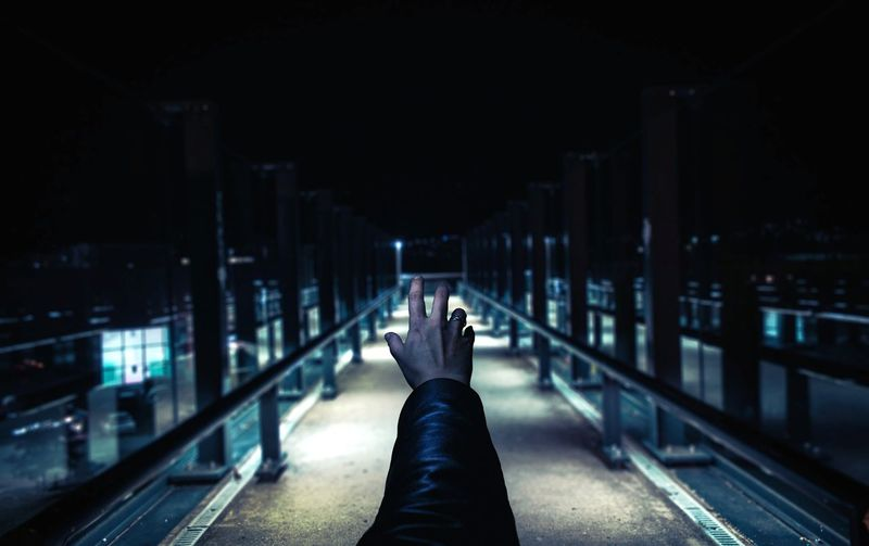 Cropped hand reaching railroad station platform at night