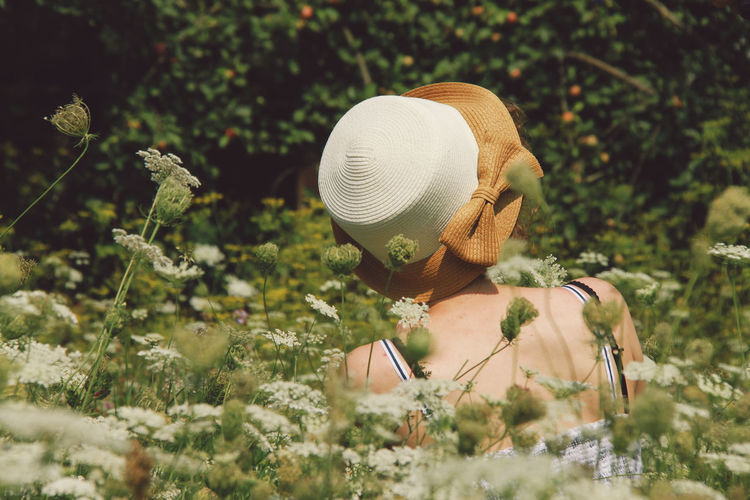 Rear view of woman wearing hat while sitting in flowering field