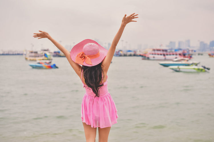 Arms Raised Beach Casual Clothing Child Childhood Clothing Focus On Foreground Hairstyle Hat Human Arm Land Leisure Activity Lifestyles Nature One Person Outdoors Pink Color Real People Rear View Sea Standing Sun Hat Three Quarter Length Water Women