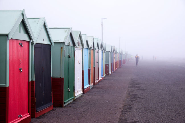 Fog In A Row Architecture Sky Day Nature Built Structure Direction The Way Forward Building Exterior Outdoors Diminishing Perspective Real People Incidental People Beach Hut Road Side By Side Protection Brighton Brighton Beach Huts,