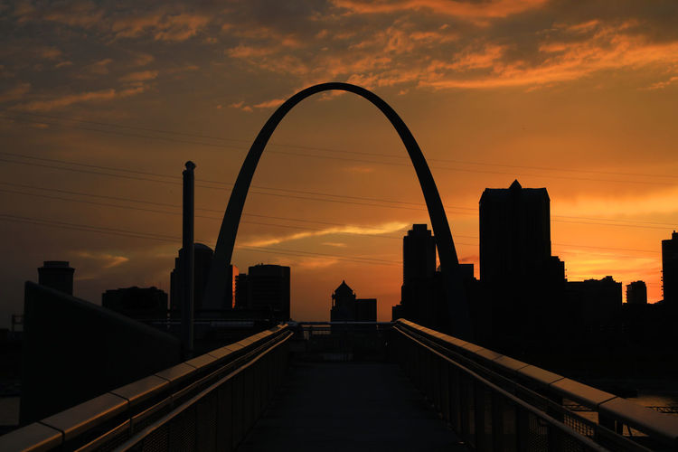 Silhouette Bridge And Buildings Against Sky During Sunset