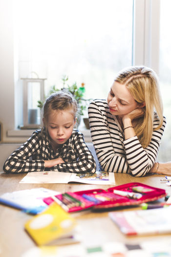 Girl Studying While Sitting With Mother At Home