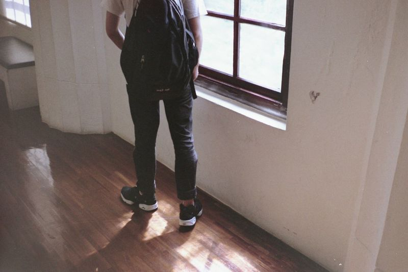 Low section of student standing on hardwood floor at home