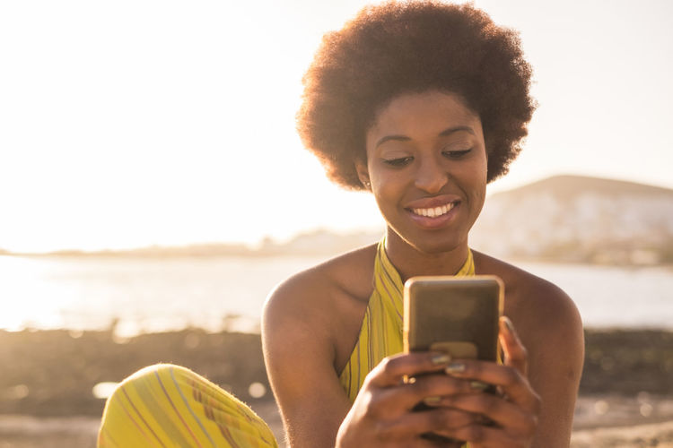 Smiling Young Woman Using Smart Phone Against Sky During Sunset