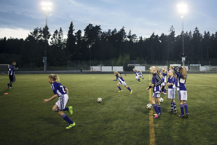People playing soccer ball on field against sky