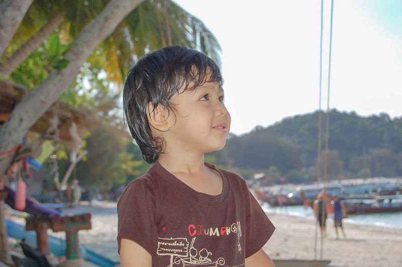 Cute boy looking away at beach