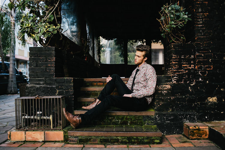 Young Man In Formalwear Sitting Outdoors