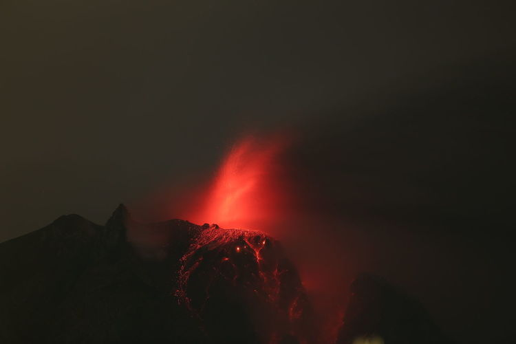 Low angle view of volcanic mountain against sky at night