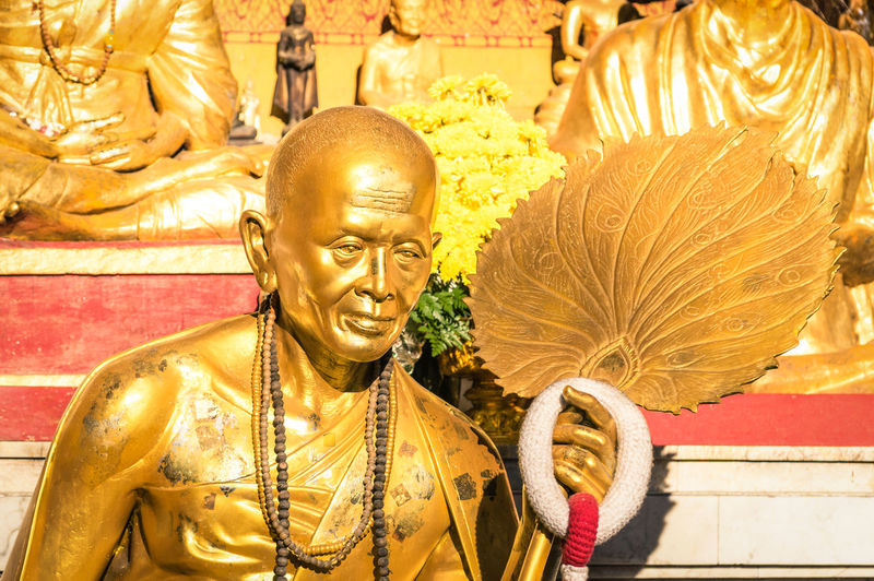Golden statue of old buddhist monk with flowers ring in the sanctuary of Doi Suthep - Ancient buddha temple in Chiang Mai province in Thailand - Concept of faith and religion in asian countries Ancient Art ASIA Asian  Asiatic  Background Beautiful Beauty Buddha Buddhism Buddhist Calm Candlelight Chiang Chiangmai Concept Culture Doi Face Famous Gold Golden Holy Landmark MAI Meditating Meditation Monk  Old Oriental Pagoda Peace People Phra Prathat Pray Religion Religious  Sculpture Spirituality Statue Suthep Temple Thai Thailand Tourism Traditional Travel Wat Worship