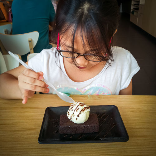 Girl eating ice cream at table