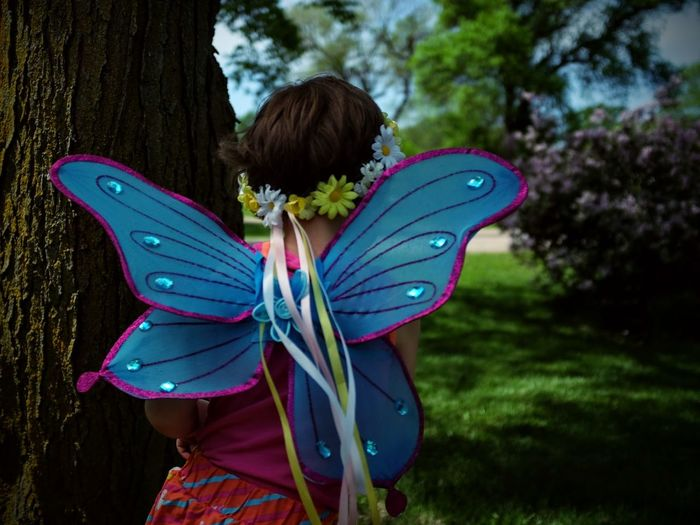 Rear View Of Girl Wearing Butterfly Costume By Tree Trunk