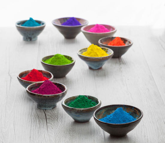 Colorful Holi powder in cups arranged in a snake shape. Shallow depth of field with back lighting. Holi Festival Bowl Close-up Colorful Day Freshness Holi Powder Indoors  Multi Colored No People Wood - Material