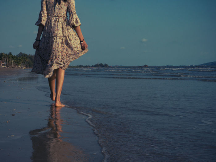 Women who wear vintage dresses are walking on the beach with excitement to relax. This summer, let's go to the sea. Water Sea Beach Low Section Land Lifestyles Real People One Person Leisure Activity Nature Women barefoot Walking Tranquility Human Leg Beauty In Nature Sky Human Body Part Outdoors