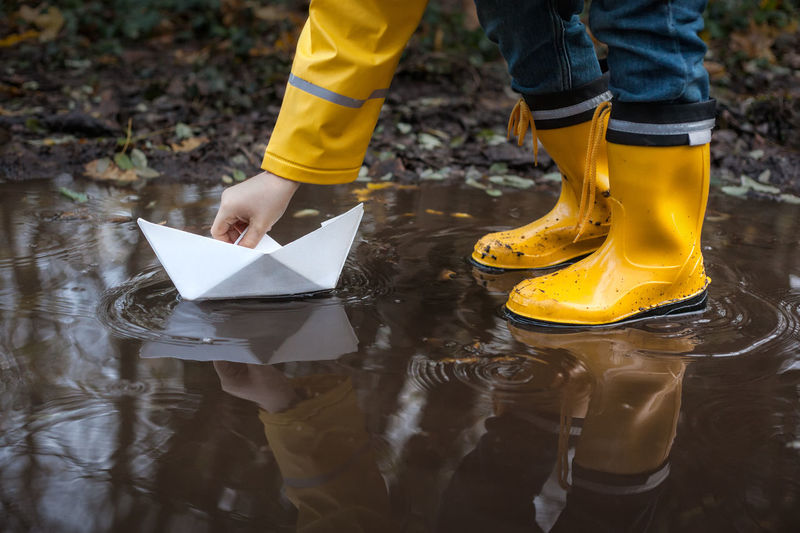 Low section of boy playing with paper boat on puddle during rainy season