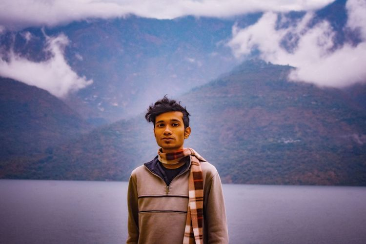 Portrait of young man standing in mountains against sky