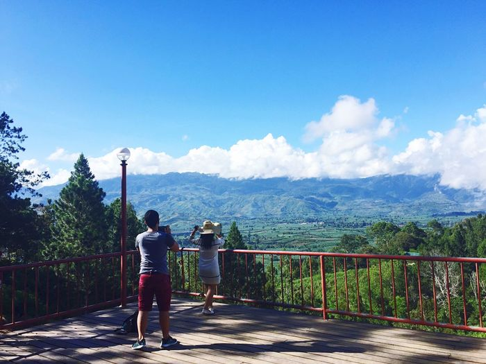 Rear View Of Friends At Observation Point Against Mountain