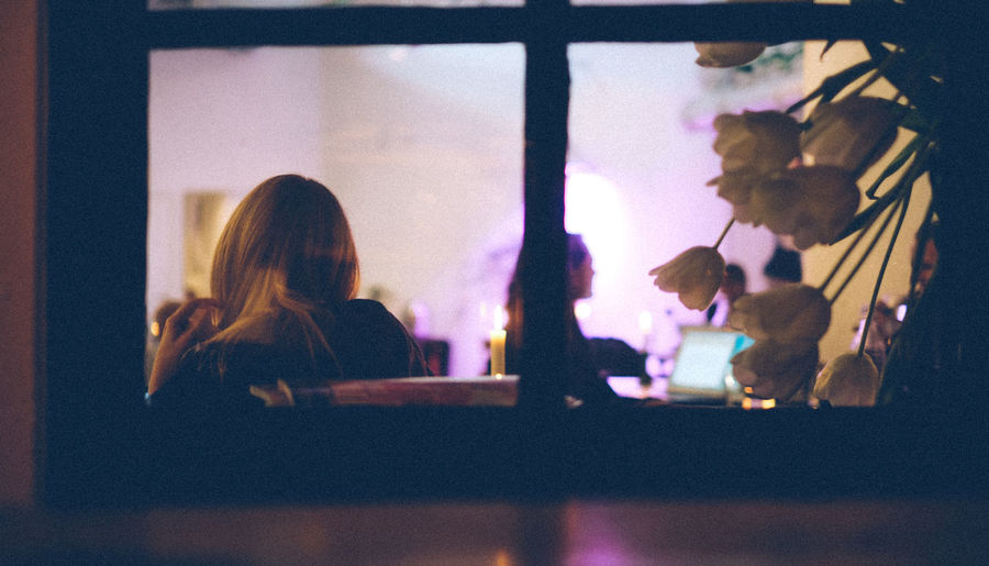 Woman Sitting In Cafe Seen Through Glass Window At Night