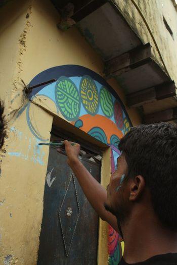 Portrait of boy holding multi colored graffiti on wall