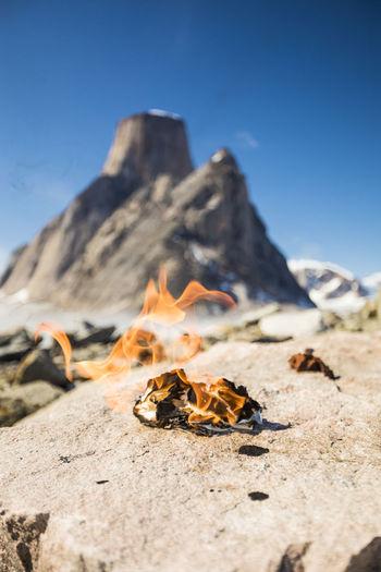 Close-up of bonfire on rock against sky