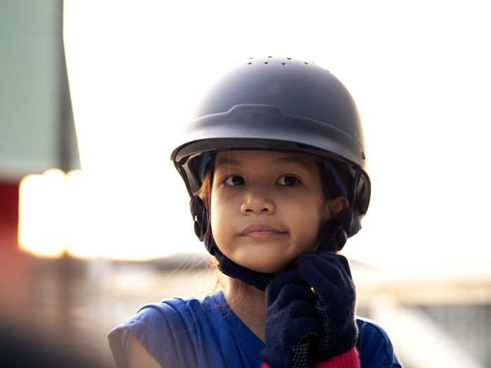 Close-up of girl wearing helmet looking away against clear sky