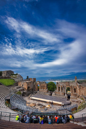 High angle view of tourists sitting at amphitheater against cloudy sky
