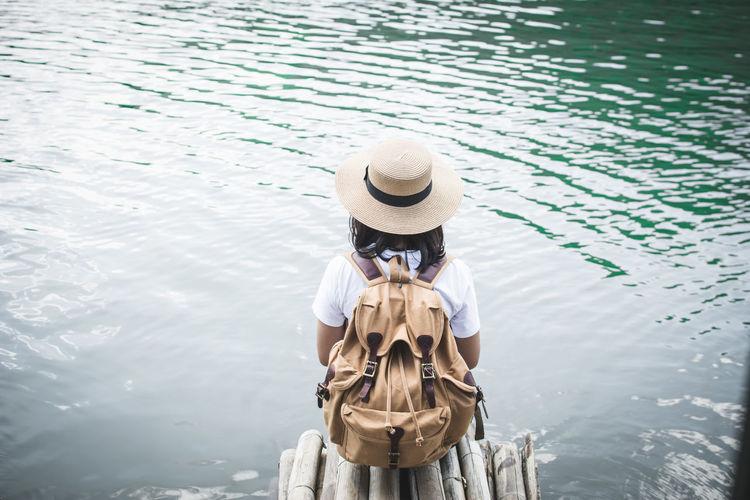 Rear View Of Woman Sitting By Lake