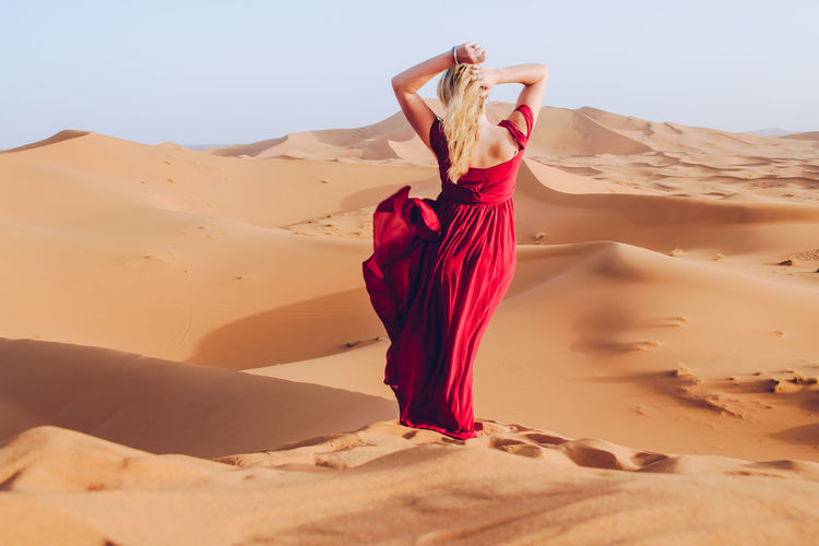 Young Woman Wearing Red Dress While Standing At Desert Against Clear Sky