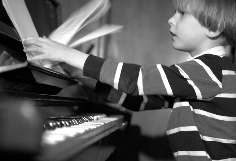 Side View Of Boy Holding Sheet Music While Sitting By Piano