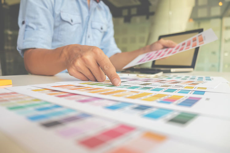 Midsection of businessman examining color swatches while sitting at table in office