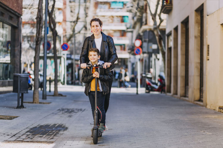 Mother and son riding electric scooter on footpath in city