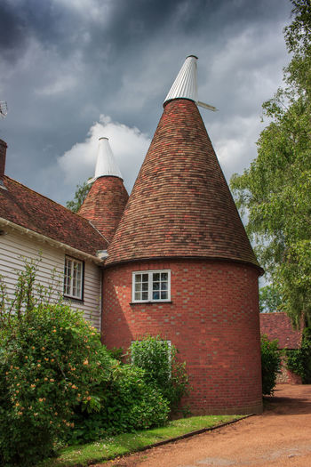 Oast House,Garden of England, Kent, England. Plant Nature No People Built Structure Architecture Building Exterior Outdoors Building Hops Beer Brewing Travel Destinations Tourism Caravan Rural Scene Countryside EyeEm Gallery Vivid International Getty Images Architecture Iconic Buildings Cloud - Sky Tree Sky Day Low Angle View Growth Brick House Wall Tower Roof Tall - High