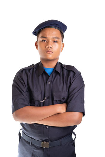 Young Asian man in police uniform isolated on white background. White Background Studio Shot Cut Out One Person Clothing Looking At Camera Standing Young Adult Cap Portrait Men Police Officer Security Face Smile Service Front View Indoors  Hat Young Men Waist Up Three Quarter Length Confidence  Teenage Boys Uniform Teenager