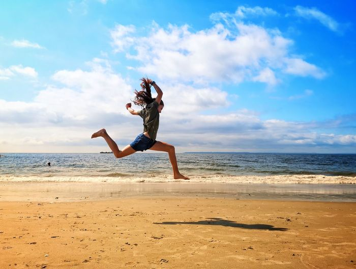 Young woman jumping on beach against sky