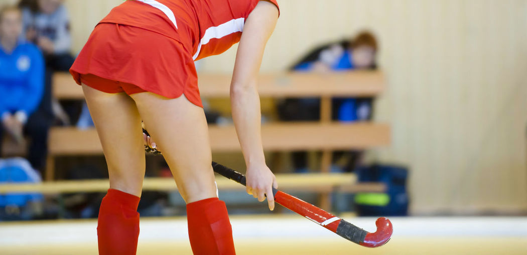 Midsection of female athlete playing hockey