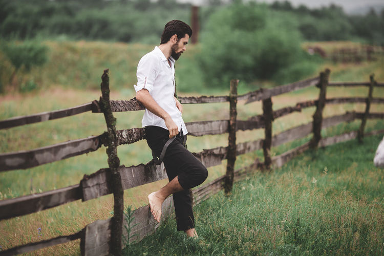 A handsome young man stands near a wooden fence and leans against it. He has a slender, attractive figure. He wears a beard. Dressed in a white classic shirt and pants with suspenders. It is barefoot in a meadow where green grass grows. In the background, nature is in all its splendor. Plants, mountains, sky with clouds. Shooting with daylight. Country Living Fashion Freedom Grass Lifestyle Looking Down Males  Man Nature Sky And Clouds Standing barefoot Beard Cloud - Sky Clouds Clouds And Sky Country Life Countryside Full Length Lifestyles Male Men One Person Portrait Sky