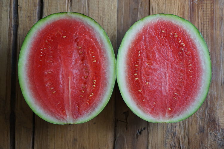 Sliced Watermelon on wooden table Green Green Color Close-up Cross Section Directly Above Food Food And Drink Freshness Fruit Halved Healthy Eating Indoors  Juicy No People Red Ripe SLICE Still Life Table Watermelon Wellbeing Wood - Material