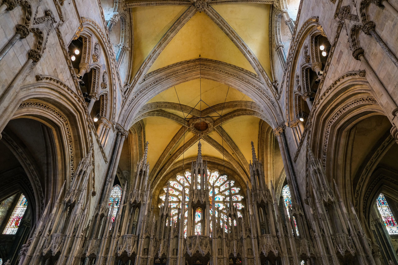 place of worship, religion, belief, spirituality, architecture, built structure, building, ceiling, arch, window, low angle view, building exterior, the past, travel destinations, history, architectural column, no people, glass, gothic style, architecture and art, altar, abbey, ornate