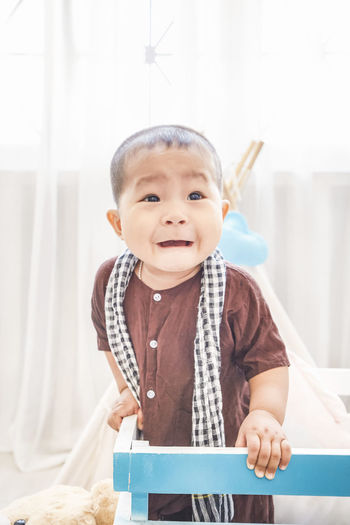Baby boy crying while standing in crib at home