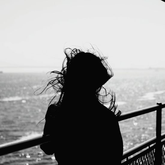 Rear view of silhouette woman standing at railing against sea