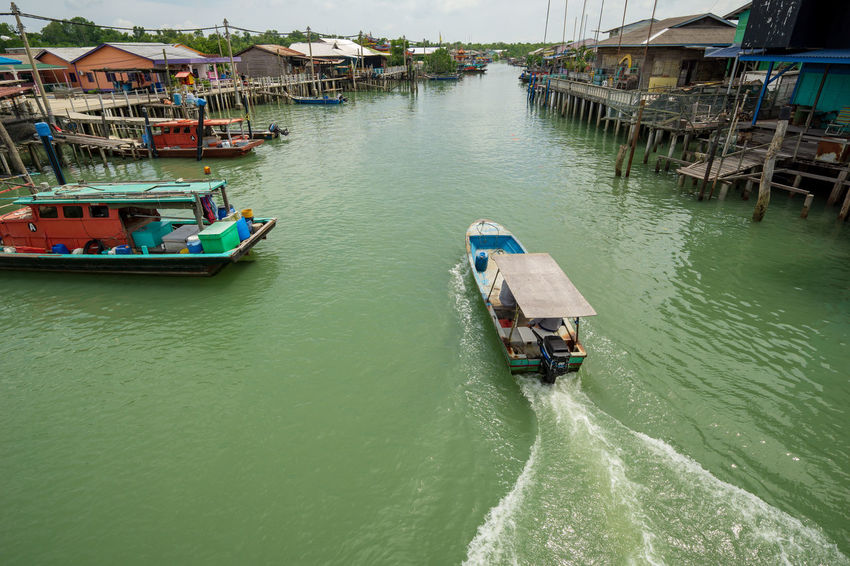 A view of a fishermen's village on stilts besides the sea in Pulau Ketam (Crab Island). This island is famous for sea food products and restaurants. Architecture Building Building Exterior Built Structure Crab Island Day High Angle View House Incidental People Mode Of Transportation Motion Nature Nautical Vessel Outdoors Pulau Ketam Malaysia Residential District River Transportation Water Waterfront